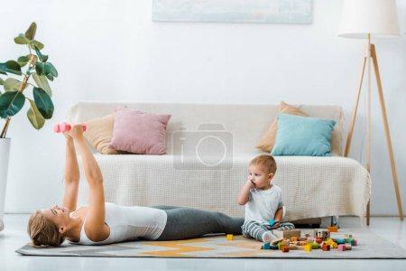 Foto de Mujer acostado en la alfombra y hacer ejercicio con pesas y niño lindo chico sentado cerca de cubos multicolores de madera en sala de estar - Imagen libre de derechos