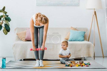 Foto de Atractiva mujer haciendo ejercicio con pesas y que chico lindo niño sentado en la alfombra cerca de los cubos multicoloras en sala de estar - Imagen libre de derechos