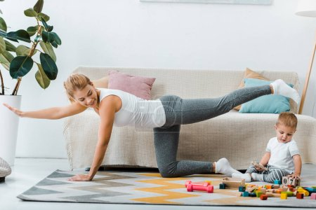 woman exercising near couch and looking at toddler boy playing with multicolored wooden cubes on carpet in living room