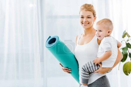 Photo pour Belle femme tenant tapis de fitness bleu et sourire mignon tout-petit garçon - image libre de droit