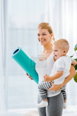 beautiful woman in sportswear holding blue fitness mat and adorable toddler boy