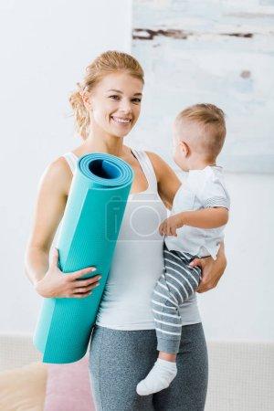 uśmiechnięta kobieta trzyma Mata fitness i toddler chłopiec i patrząc na kamery w domu