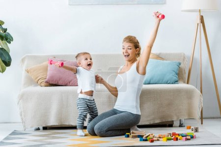 beautiful mother and cute toddler son holding dumbbells in raising hands and laughing in living room