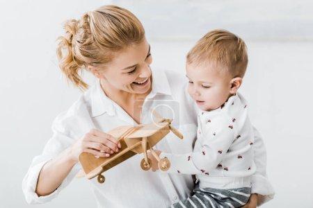 Photo pour Femme souriante tenant modèle bleue et jouant avec garçon mignon bambin à la maison - image libre de droit