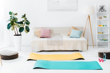 Photo for Interior of living room with fitness mats and sport equipment on floor - Royalty Free Image
