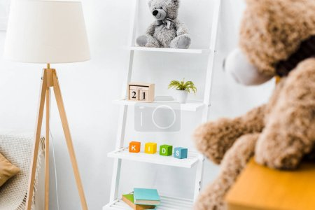 modern interior of nursery room with rack and toys