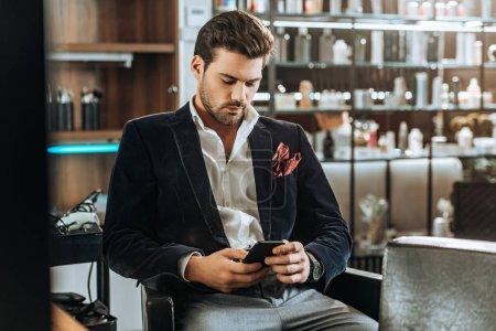 Photo pour Élégant beau jeune homme en utilisant smartphone tout en étant assis dans un salon de beauté - image libre de droit