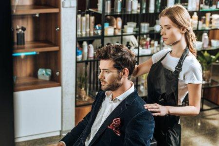 Photo pour Vue grand angle de coiffeur faisant coiffure à beau jeune homme dans le salon de beauté - image libre de droit