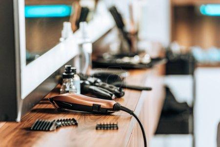 Photo pour Vue rapprochée de la tondeuse électrique sur étagère en bois dans le salon de beauté - image libre de droit