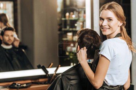 Photo pour Beau jeune coiffeur souriant à la caméra tout en peignant les cheveux au client masculin dans le salon de beauté - image libre de droit