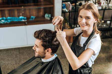 high angle view of hairstylist smiling at camera while cutting hair to handsome client in beauty salon