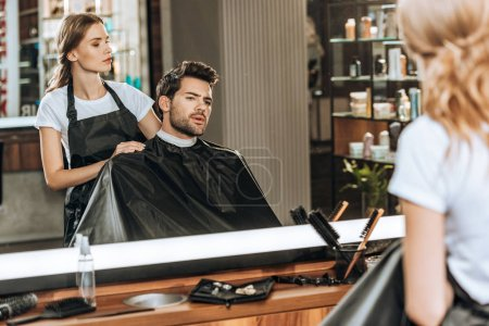 female hairstylist cutting hair to handsome young man in beauty salon