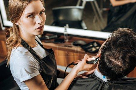 Photo pour Vue grand angle de jeune coiffeur en utilisant une tondeuse électrique et en regardant la caméra tout en travaillant avec le client dans un salon de beauté - image libre de droit