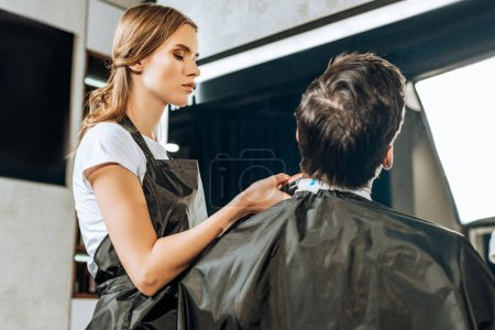 young hairdresser using electric hair clipper while working with client in beauty salon