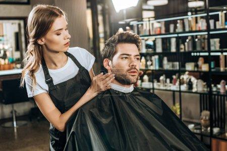 Photo pour Beau jeune coiffeur faisant coiffure à beau client masculin dans le salon de beauté - image libre de droit