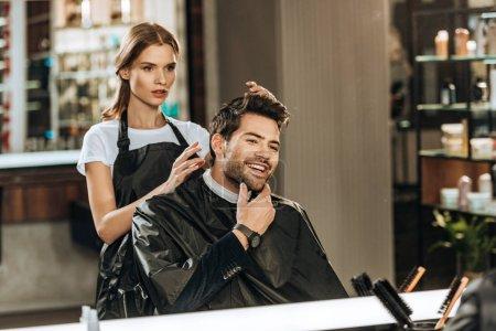 Photo pour Jeune coiffeuse et bel homme souriant regardant miroir dans le salon de beauté - image libre de droit