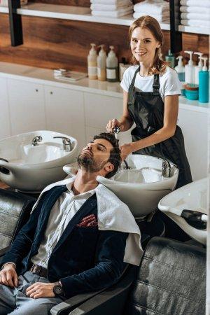 Photo pour Vue grand angle du coiffeur souriant à la caméra tout en lavant les cheveux à beau jeune homme dans le salon de beauté - image libre de droit