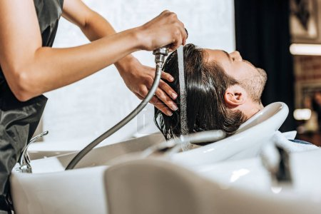Photo for Partial view of hairdresser washing hair to handsome young man in beauty salon - Royalty Free Image