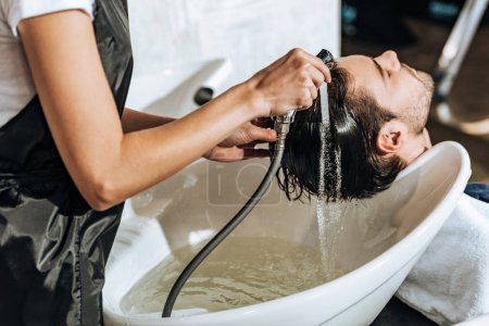 partial view of hairstylist washing hair to handsome young male client in beauty salon