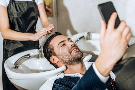 Photo pour Plan recadré de coiffeur laver les cheveux à l'homme souriant prendre selfie avec smartphone dans le salon de beauté - image libre de droit