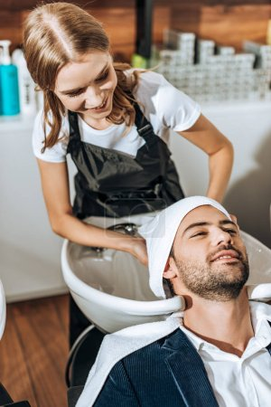 high angle view of young hairdresser washing hair to smiling handsome man in beauty salon