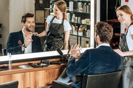Photo pour Souriant jeune coiffeur regardant beau client heureux montrant ok signe et regardant miroir dans le salon de beauté - image libre de droit