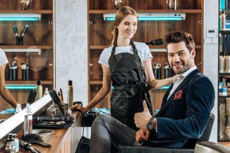 Photo pour Souriant jeune coiffeur regardant beau client heureux montrant pouce dans le salon de beauté - image libre de droit