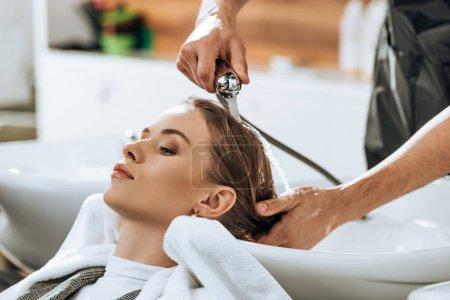 Photo pour Vue partielle de coiffeur laver les cheveux à la jeune femme attrayante dans le salon de beauté - image libre de droit