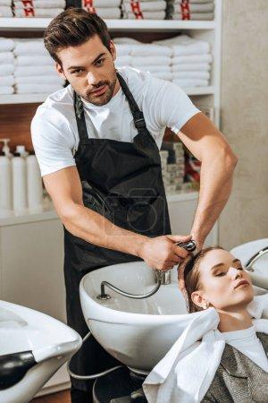 Photo pour Beau jeune coiffeur regardant la caméra tout en lavant les cheveux à la femme dans le salon de beauté - image libre de droit