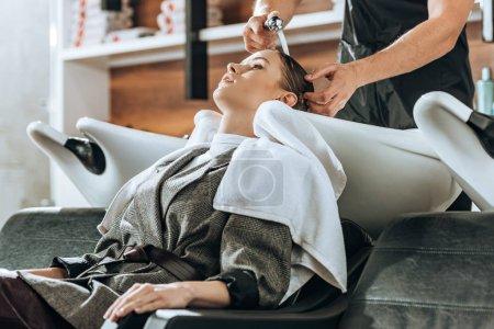 Photo pour Plan recadré de coiffeur laver les cheveux à la jeune femme attrayante dans le salon de beauté - image libre de droit