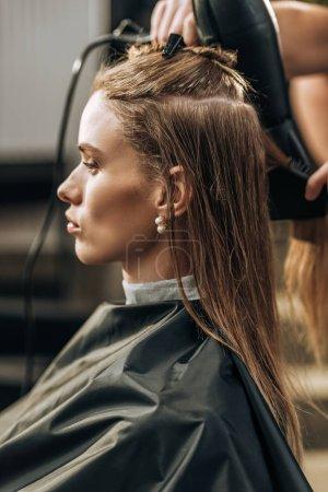 Photo pour Plan recadré de cheveux coiffeur séchant à belle jeune femme dans le salon de beauté - image libre de droit