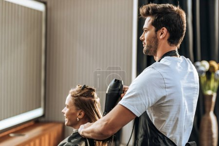 handsome young hairdresser drying hair to attractive girl in beauty salon