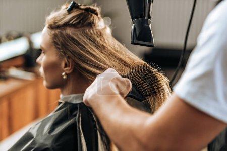 Photo pour Plan recadré de coiffeur séchage des cheveux à la fille attrayante dans le salon de beauté - image libre de droit