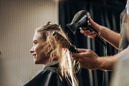 Photo pour Plan recadré de coiffeur séchant les cheveux à la fille souriante dans le salon de beauté - image libre de droit