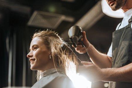 Photo pour Vue à angle bas de coiffeur peignage et séchage des cheveux à belle jeune femme dans le salon de beauté - image libre de droit