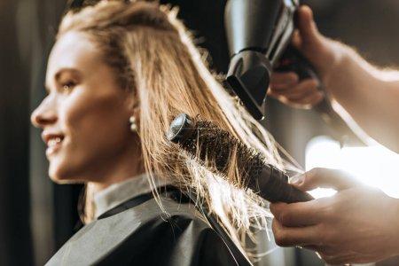 Photo pour Gros plan vue partielle de coiffeur peignage et séchage des cheveux à belle jeune femme dans le salon de beauté - image libre de droit