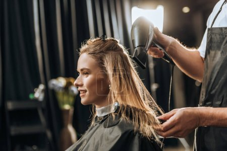 Photo for Cropped shot of hairstylist combing and drying hair to beautiful young woman in beauty salon - Royalty Free Image