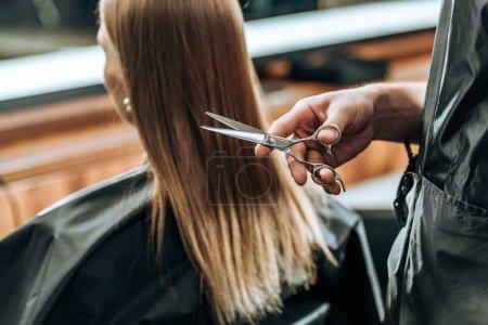 Photo pour Plan recadré de coiffeur tenant des ciseaux et jeune femme visitant salon de beauté - image libre de droit