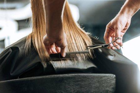 Photo pour Coiffeur couper les cheveux à belle jeune femme dans le salon de beauté - image libre de droit