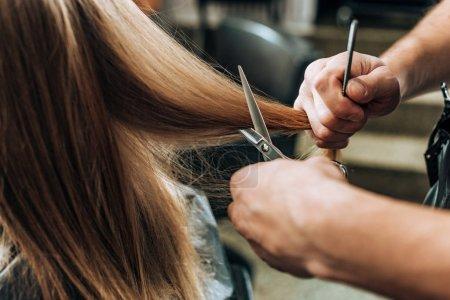 Photo pour Plan recadré de coiffeur faisant coupe de cheveux à la jeune femme dans le salon de beauté - image libre de droit