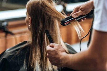 Photo pour Plan recadré de coiffeur tenant peigne et en utilisant un lisseur dans le salon de beauté - image libre de droit