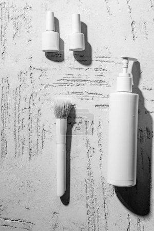 Photo pour Vue rapprochée du décoratifs blancs vernis à ongles, brosse et conteneur sur le mur dans un salon de beauté - image libre de droit