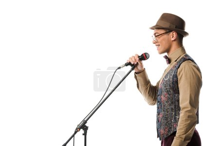 side view of smiling mixed race male musician in hat singing in microphone isolated on white