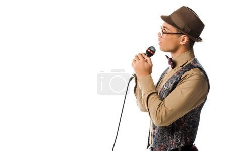 side view of mixed race male musician in hat singing in microphone isolated on white