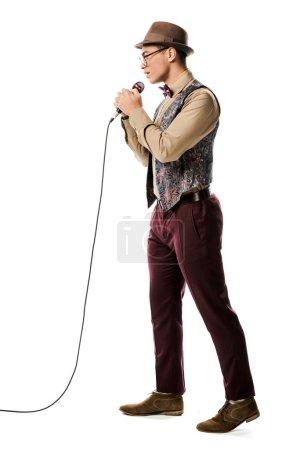 Photo pour Musicien mâle jeune métisse dans le chant de chapeau micro isolé sur blanc - image libre de droit