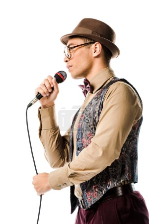 low angle view of mixed race male musician in hat singing in microphone isolated on white