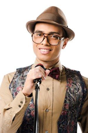 Photo pour Portrait du musicien jeune mâle race mixte dans le chant de chapeau micro isolé sur blanc - image libre de droit