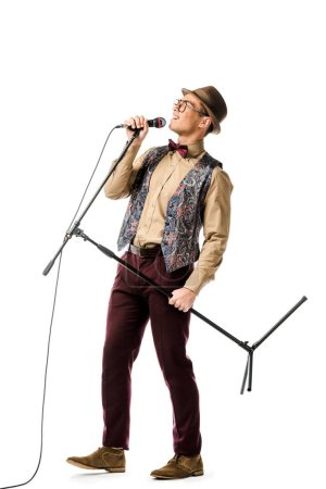 young emotional mixed race male musician holding microphone and singing isolated on white