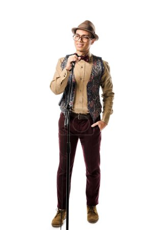 joyful young mixed race man in stylish hat and eyeglasses singing in microphone isolated on white