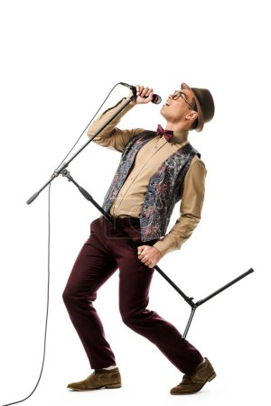 emotional stylish mixed race male musician holding microphone and singing isolated on white